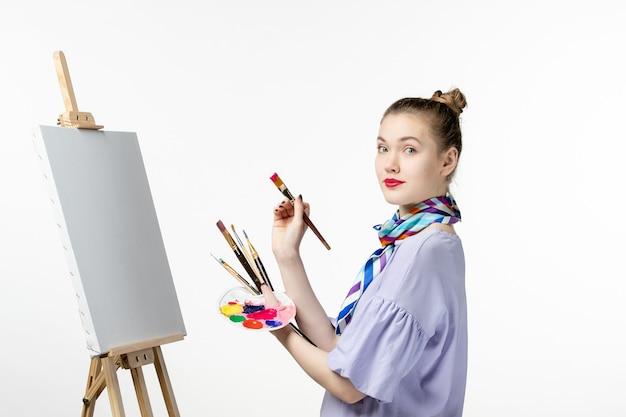 Widok z przodu kobieta malarka przygotowująca się do rysowania na białej ścianie farba obraz sztuki zdjęcie rysunek ołówek sztalugowy