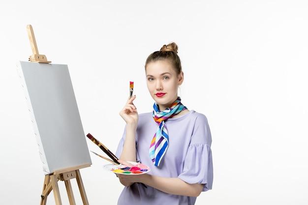 Widok z przodu kobieta malarka przygotowująca się do rysowania na białej ścianie sztaluga farba obraz rysunek artysta ołówek fotografia sztuka