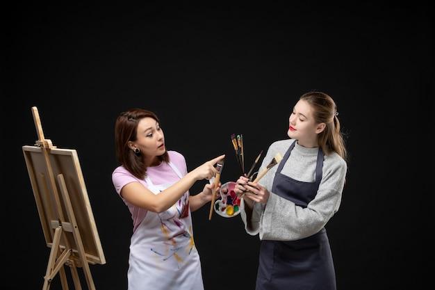 Widok z przodu kobieta malarka rysująca na sztalugach z inną kobietą na czarnej ścianie artysta zdjęcie kolor sztuka obraz malowanie rysowanie