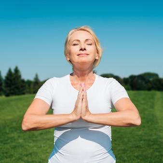 Widok z przodu kobieta medytuje na zewnątrz