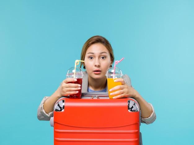 Widok z przodu kobieta na wakacjach trzyma świeże napoje na jasnoniebieskim tle podróż rejs wakacje podróż samolotem morskim