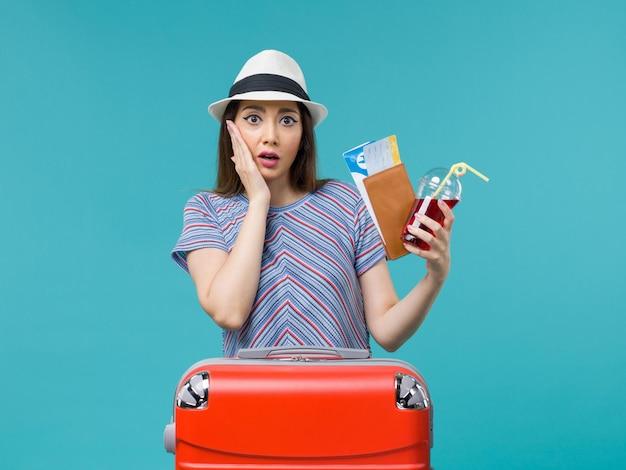Widok z przodu kobieta na wakacjach trzymając portfel z biletami na niebieskim tle podróż rejs kobieta samolotem latem