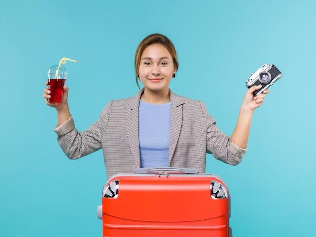 Widok z przodu kobieta na wakacjach trzymając sok z aparatem na niebieskim tle podróż rejs wakacje podróż samolotem morskim