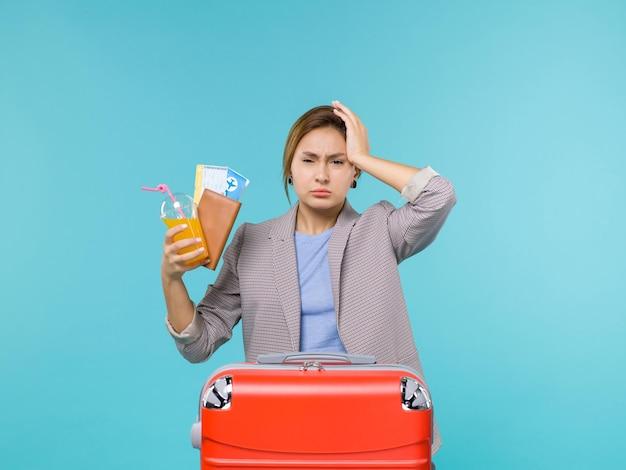 Widok z przodu kobieta na wakacjach trzymając świeży napój i bilety na niebieskim tle wycieczka morska podróż wakacyjna podróż