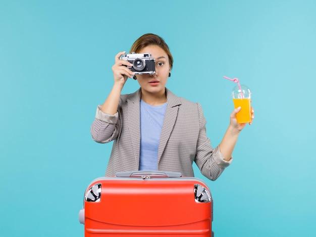 Widok z przodu kobieta na wakacjach, trzymając świeży sok i aparat na jasnoniebieskim tle podróż morska podróż wakacje