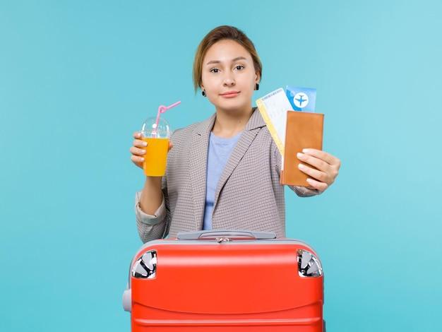 Widok z przodu kobieta na wakacjach, trzymając świeży sok i bilety na jasnoniebieskim tle morze wakacje samolot podróż podróż podróż