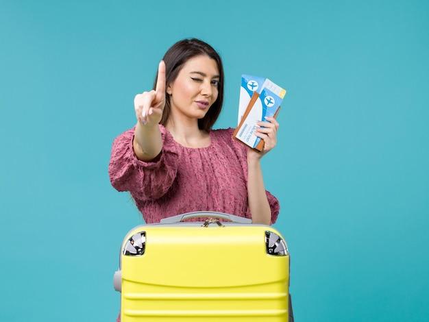Widok z przodu kobieta na wakacjach trzymająca bilety na niebieskim tle podróż letnia wycieczka kobieta morze ludzi