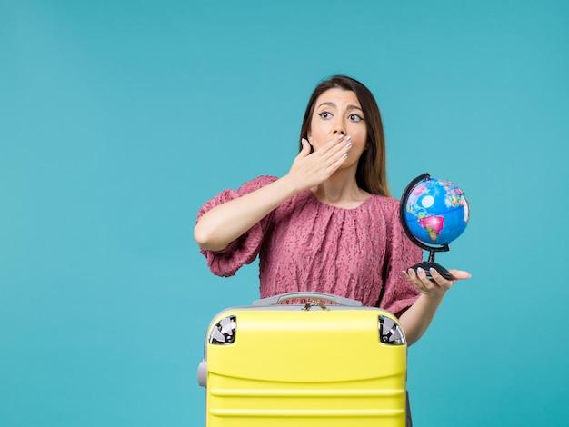 Widok z przodu kobieta na wakacjach trzymająca małą kulę ziemską na jasnoniebieskim tle morska wycieczka wakacje podróż lato kobieta