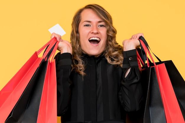 Widok z przodu kobieta niosąca czarne i czerwone torby na zakupy