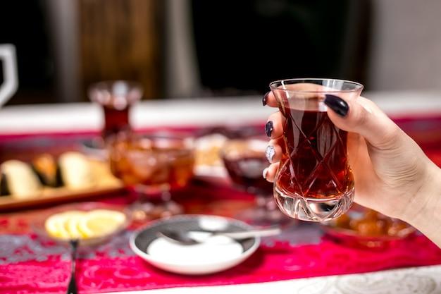 Widok z przodu kobieta pije herbatę ze szklanego armudu