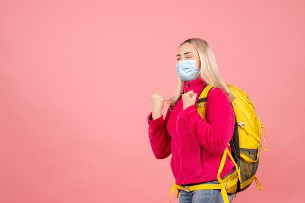 Widok z przodu kobieta podróżnik z żółtym plecakiem w masce pokazujący zwycięski gest z zamkniętymi oczami