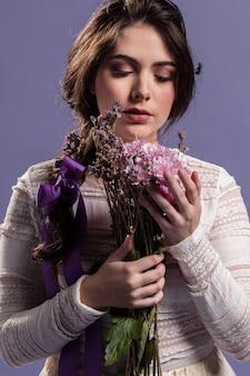 Widok z przodu kobieta podziwiając bukiet kwiatów