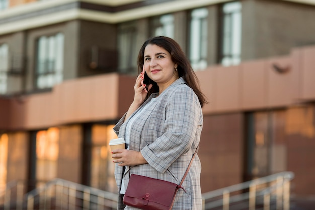 Widok z przodu kobieta rozmawia przez telefon na zewnątrz