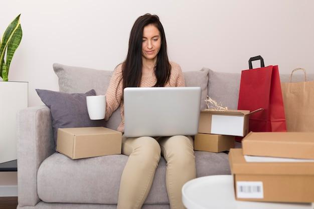 Widok z przodu kobieta siedzi na kanapie podczas sprawdzania swojego laptopa