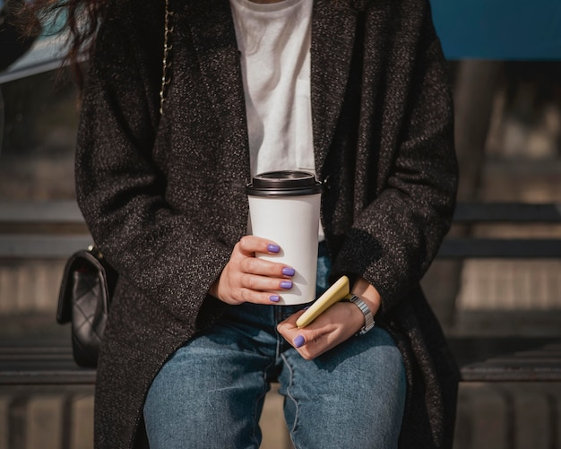 Widok z przodu kobieta trzyma kawę i czeka na autobus