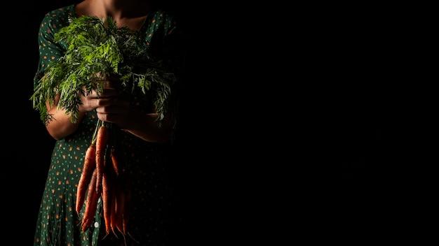 Widok z przodu kobieta trzyma marchewki z kopiowaniem przestrzeni