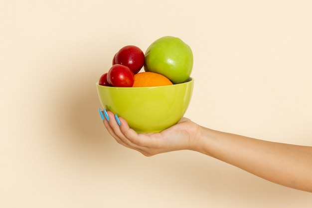 Widok z przodu kobieta trzyma talerz z różnymi owocami na beżu