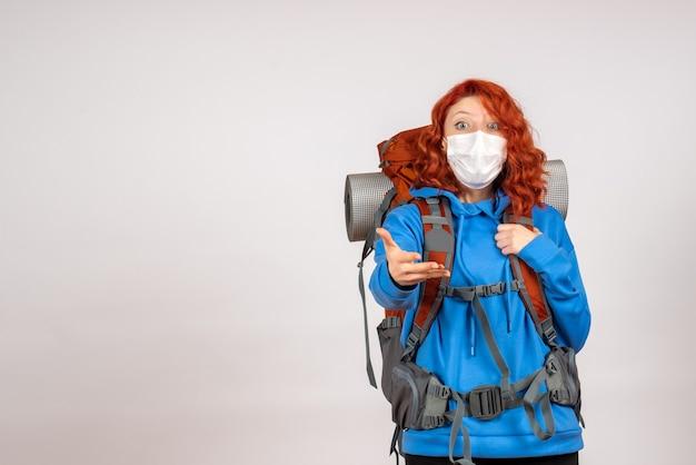Widok z przodu kobieta turysta w górach w masce z plecakiem