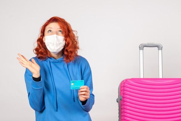 Widok z przodu kobieta turysta w masce trzymając kartę bankową