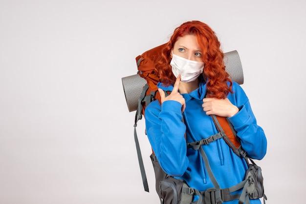 Widok z przodu kobieta turysta w masce z jej plecakiem myśli