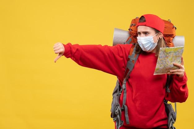 Widok z przodu kobieta turysta z plecakiem i maską trzymając mapę dając kciuk w dół