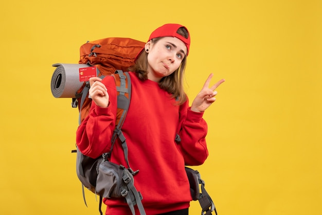 Widok z przodu kobieta turysta z plecakiem trzymając kartę rabatową, gestykulując znak zwycięstwa