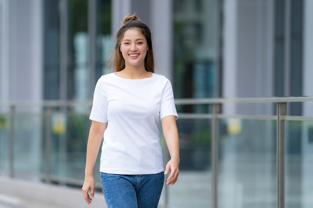 Widok z przodu, kobieta w białej koszulce i niebieskich dżinsach, stojąca na ulicy miasta, letni dzień