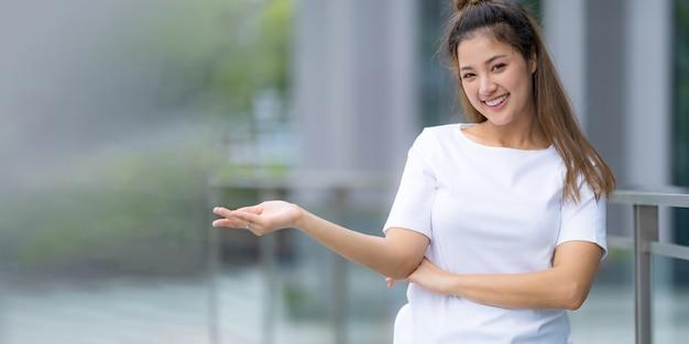 Widok z przodu, kobieta w białej koszulce i niebieskich dżinsach, stojąca na ulicy miasta