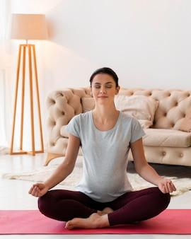 Widok z przodu kobieta w ciąży medytuje w pomieszczeniu
