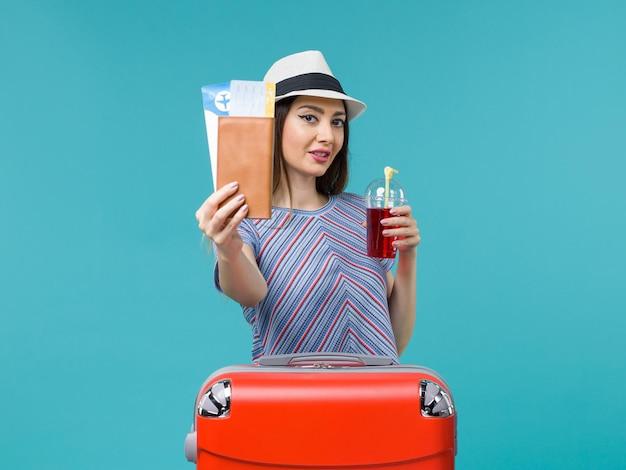 Widok z przodu kobieta w wakacje trzymając bilety i czerwony sok na niebieskim tle podróż morska podróż kobiet wakacje
