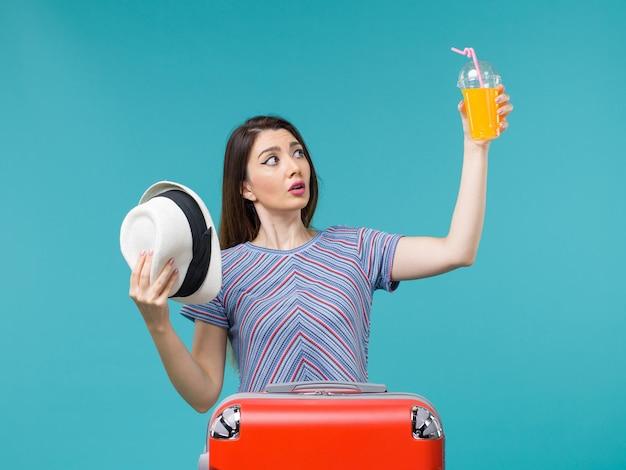Widok z przodu kobieta w wakacje trzymając sok i kapelusz na niebieskim tle rejsu wakacje wycieczka morska podróż