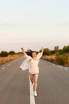 Widok z przodu kobiety biegnącej na zewnątrz pośrodku drogi