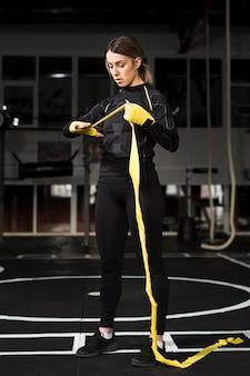 Widok z przodu kobiety bokser owijania dłoni w ramach przygotowań do praktyki