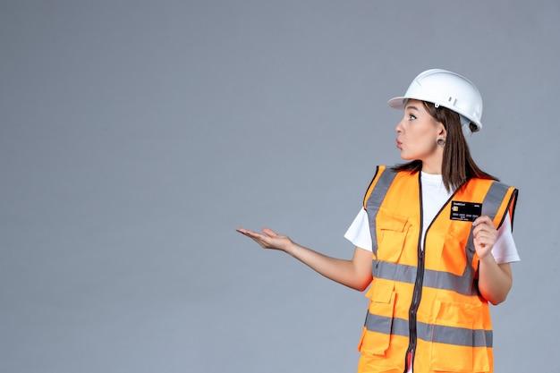 Widok z przodu kobiety budowniczego z czarną kartą bankową w dłoniach na szarej ścianie