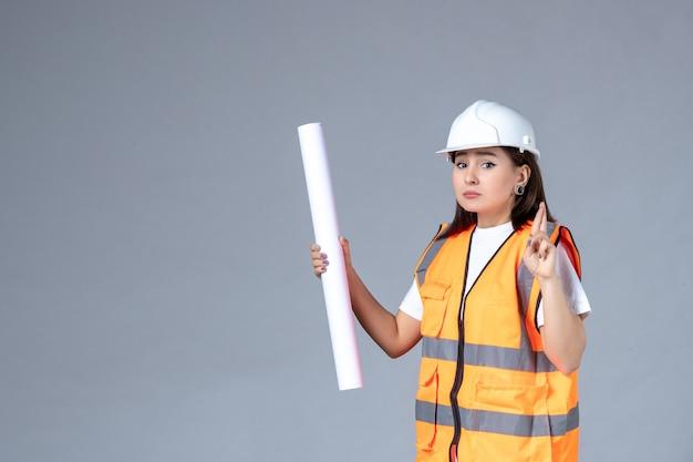 Widok z przodu kobiety budowniczego z plakatem w dłoniach na szarej ścianie
