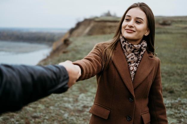 Widok z przodu kobiety ciągnącej swojego chłopaka na zewnątrz