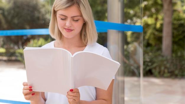 Widok z przodu kobiety czytanie książki na zewnątrz
