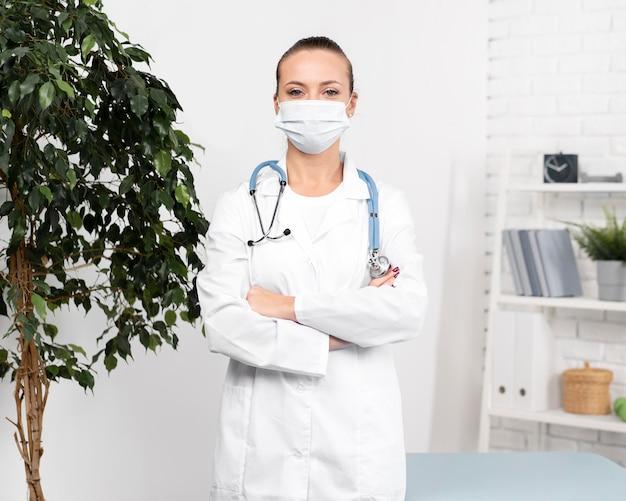 Widok z przodu kobiety fizjoterapeuty z maską medyczną i stetoskopem