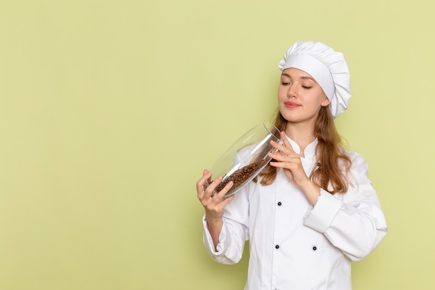 Widok z przodu kobiety kucharza w białym garniturze kucharza gospodarstwa może pełne ziaren kawy na zielonym biurku kuchnia kuchnia gotowanie posiłku żeński kolor