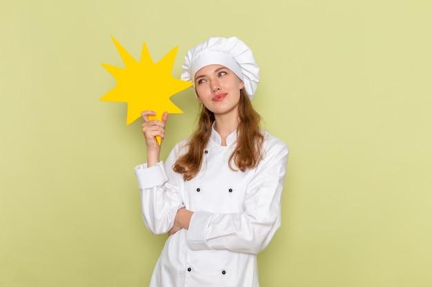 Widok z przodu kobiety kucharza w białym garniturze kucharza myśli i trzyma żółty znak na zielonej ścianie