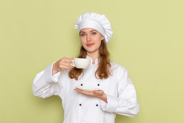 Widok z przodu kobiety kucharza w białym garniturze, trzymając kubek i uśmiechając się na zielonej ścianie