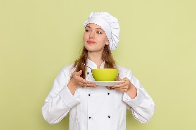 Widok z przodu kobiety kucharza w białym garniturze, trzymając zielony talerz z naczyniem na zielonej ścianie