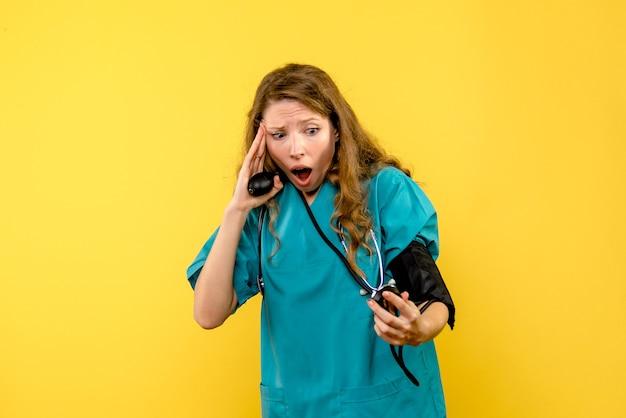 Widok z przodu kobiety lekarz pomiaru ciśnienia na żółtej ścianie