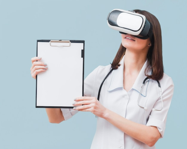 Widok z przodu kobiety lekarz trzymając notatnik podczas noszenia słuchawki wirtualnej rzeczywistości