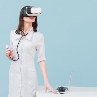 Widok z przodu kobiety lekarz z wirtualnej rzeczywistości zestaw słuchawkowy i stetoskop