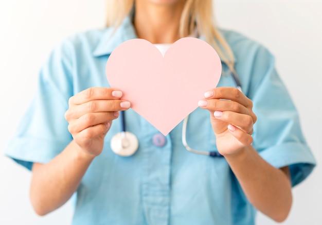 Widok z przodu kobiety lekarz ze stetoskopem trzymając papierowe serce