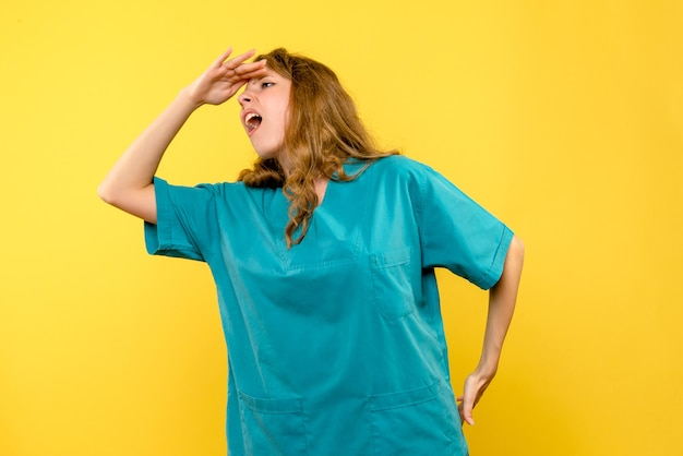 Widok z przodu kobiety lekarza patrząc na żółtą ścianę