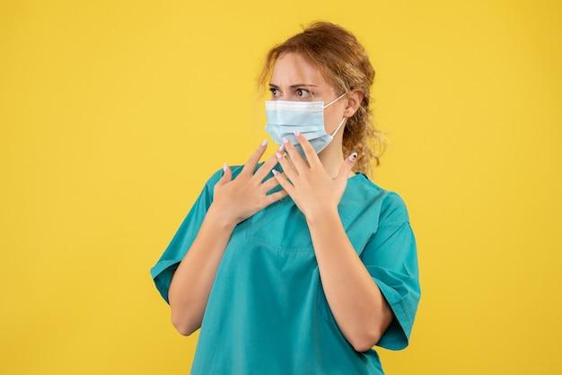 Widok z przodu kobiety lekarza w garniturze i masce na żółtej ścianie