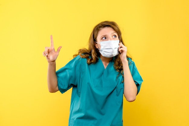 Widok z przodu kobiety lekarza w masce na żółtej ścianie