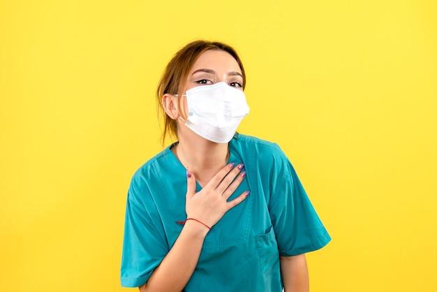 Widok z przodu kobiety lekarza weterynarii na sobie maskę na żółtej ścianie